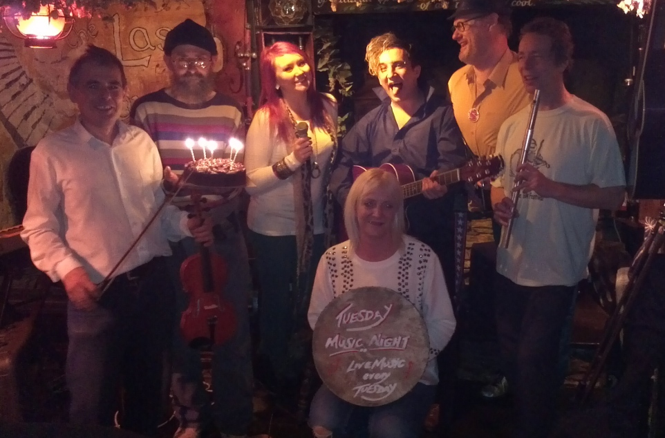 Photo of musicians and staff of the Last Inn on music nights 5th anniversary. Timbo holds the cake with five candles!